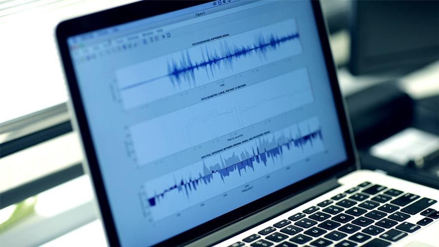Laptop with signal processing in MATLAB running, showing three time-domain voice signals.