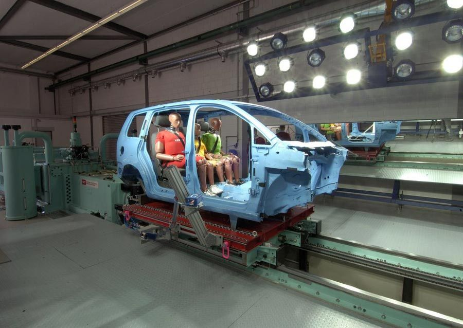 Three crash test dummies in back seat of automobile chassis with doors and front assembly removed.