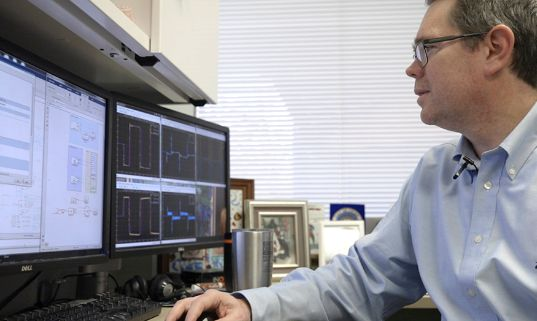 Kottenstette is seated in his office. The computer screen on the left shows Simulink Real-Time models.