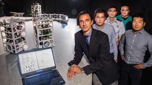Prof. Marcello Romano and the NPS Spacecraft Robotics Lab research team with the POSEIDYN test bed and floating spacecraft simulators.