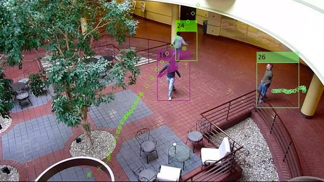 A lobby with people walking. Trails show trajectories of each tracked individual.